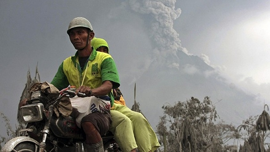 Nov. 6: Villagers ride on their motorcycle as Mount Merapi spewing volcanic materials in the background in Srumbung, Central Java, Indonesia.