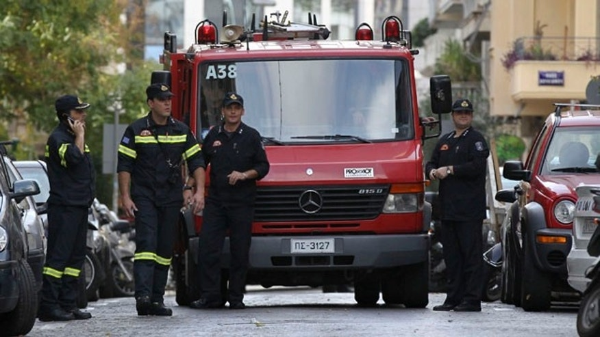 Nov. 9: Firefighters stand outside the Hungarian Embassy after bomb experts destroyed a suspicious package, in a controlled explosion, in the upmarket Athens district of Kolonaki.