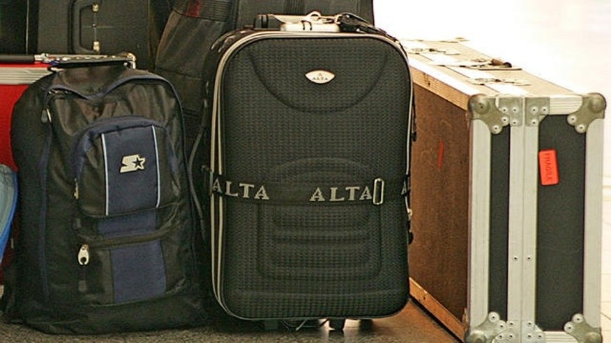 A traveler sleeps next to some luggage at LaGuardia Airport  in New York, Friday, Aug. 11, 2006.  Passengers in the United States are facing heightened security and delays at airports today after authorities in London uncovered a terror plot yesterday aimed at airlines traveling from Britain to the U.S.    (AP Photo/Ed Betz)