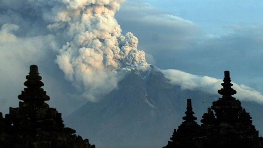Mount Merapi spews massive clouds of ash behind Prambanan temple in Klaten, Indonesia, Wednesday, Nov. 10, 2010. The volcano has forced U.S. President Barack Obama to cut short his visit to the country, and some international airlines are canceling flights over concerns about air safety Wednesday.