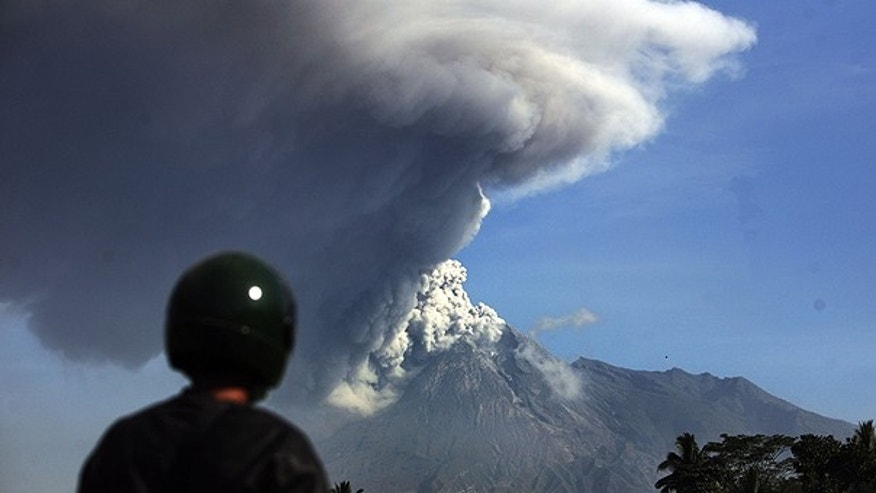 Nov. 12: A man watches Mount Merapi spews volcanic material as seen from Argomulyo, Indonesia.