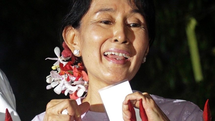 Nov. 13: Burma's pro-democracy leader Aung San Suu Kyi talks to the supporters at the gates of her home after she was freed by the military junta.