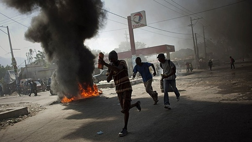 Nov. 18: Demonstrators run past burning tires during a protest in Port-au-Prince, Haiti. Protesters in Haiti's capital clashed with police following days of rioting in northern Haiti over suspicions that U.N. soldiers introduced a cholera epidemic that has killed more than 1,000 people.