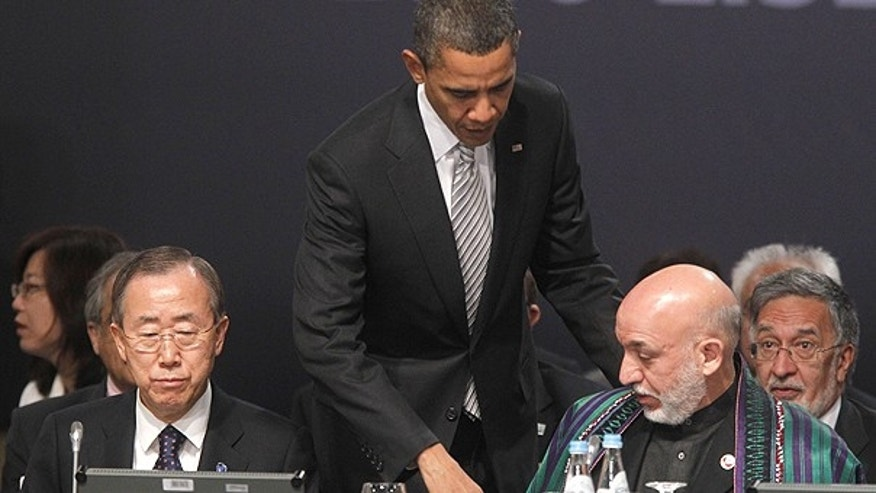 Nov. 20: President Barack Obama, center, walks over to greet Afghanistan President Hamid Karzai, right, seated, during the start of the Afghanistan Opening Session at NATO Summit in Lisbon, Portugal.
