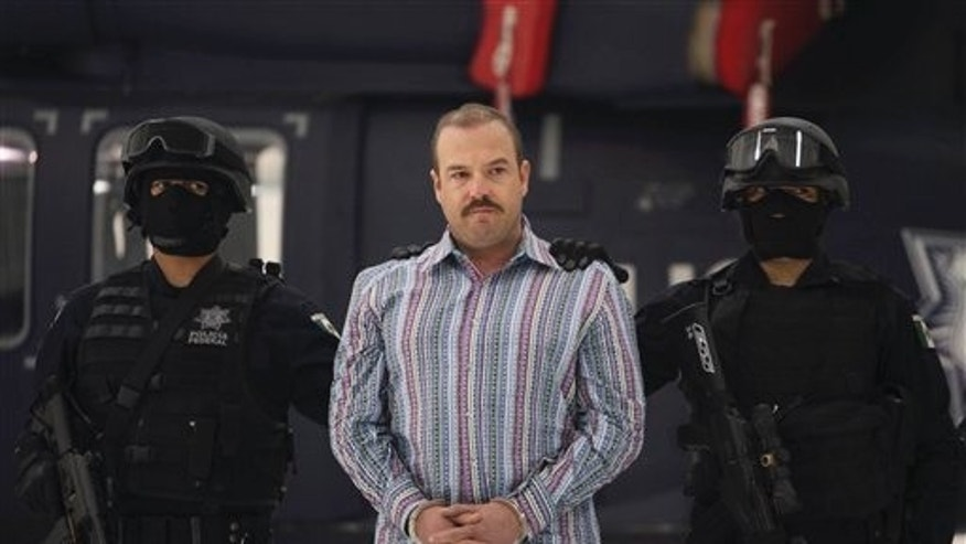 "Federal Police officers escort accused drug trafficker Carlos Montemayor during a presentation for the media in Mexico City, Wednesday, Nov. 24, 2010. According to Federal Police Montemayor took over the criminal organization led by Edgar Valdez Villareal, aka ""La Barbie"", a reputed US-born kingpin after he was detained. (AP Photo/Alexandre Meneghini)"