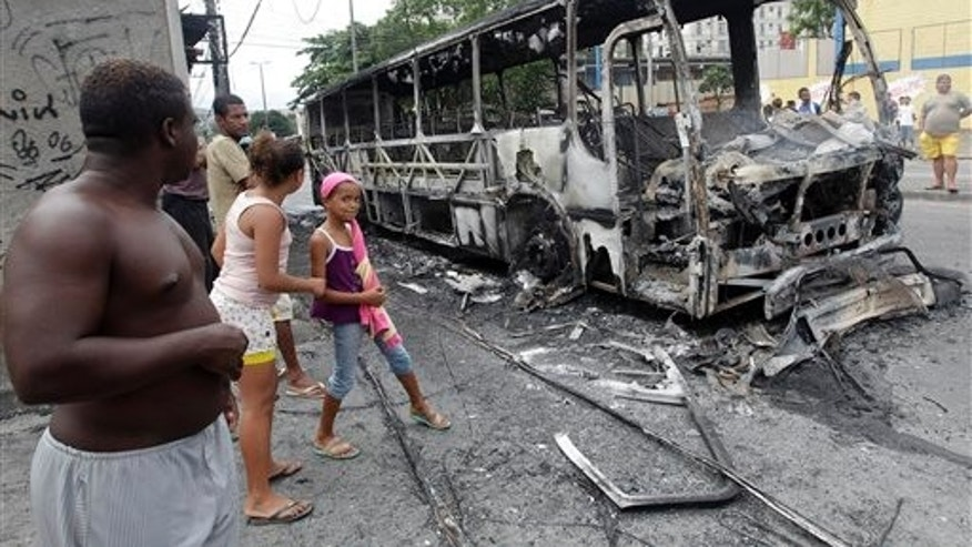 Residents watch a bus burned  by alleged drug traffickers at the Santa Cruz slum in Rio de Janeiro, Brazil, Wednesday, Nov. 24, 2010. Heavily armed men halted buses and cars, robbed their passengers and set the vehicles ablaze Wednesday in Rio de Janeiro, continuing a wave of violence that has rattled rich and poor alike in a city Brazil hopes to make a showplace for the 2016 Olympics. (AP Photo/Silvia Izquierdo)