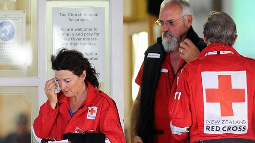 Nov. 24: Red Cross volunteers leave a candlelight vigil following a second explosion at the Pike River Coal Mines in Greymouth, New Zealand.