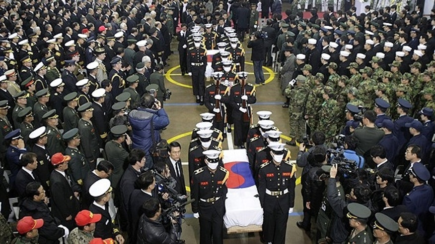 Nov. 27: South Korean marines carry two flag-draped caskets containing the remains of marines killed in Tuesday's North Korean bombardment during a funeral service at a military hospital in Seongnam, South Korea.