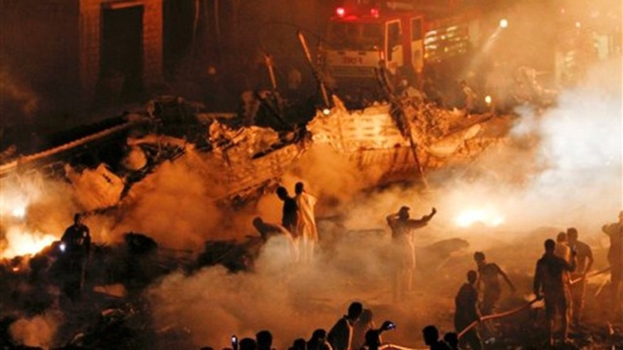 Pakistani volunteers and firefighters struggle to extinguish a fire at the site of a plane crash in Karachi, Pakistan on Sunday, Nov. 28, 2010. A cargo plane crashed into a housing complex in Pakistan's largest city soon after takeoff Sunday, setting off a huge blaze. The aircraft had eight crew on board, the civil aviation authority said.