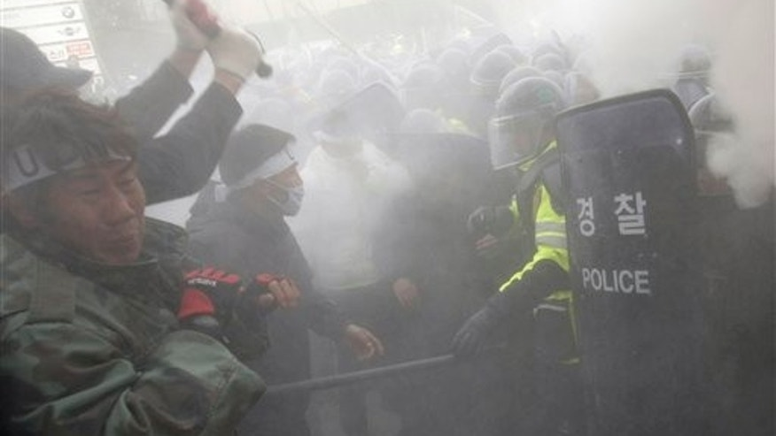 Nov. 27: Former South Korean underwater demolition team members clash with riot policemen as they spray fire extinguishers during an anti-government rally in front of the Defense Ministry in Seoul, South Korea.