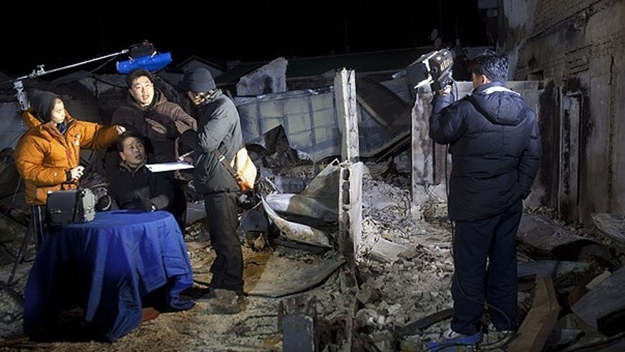 Nov. 27: A South Korean nightly news anchor prepares to give a live broadcast from a desk set up on top of the rubble in a destroyed neighborhood on Yeonpyeong Island, South Korea.