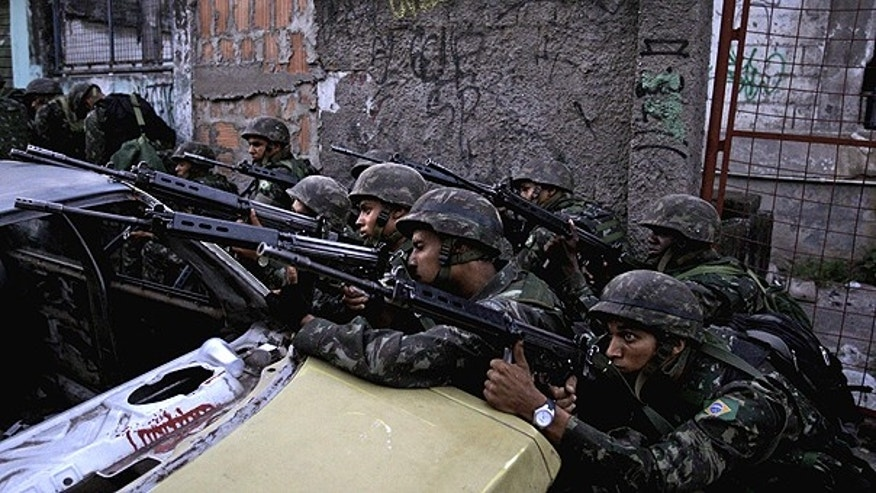 Nov. 27: Soldier aim their weapons during an operation against drug traffickers at the Complexo do Alemao slum in Rio de Janeiro, Brazil.