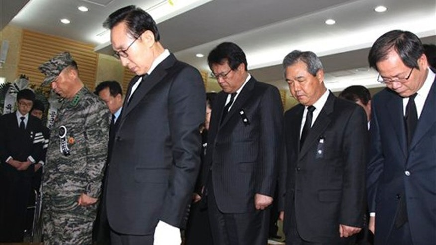 South Korean President Lee Myung-bak, second from left, and his cabinet members take moment of silence during a memorial service for South Korean Marines killed in a North Korean bombardment, at a military hospital in Seongnam, South Korea, Friday, Nov. 26, 2010.