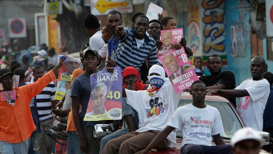 Supporters of Haiti's presidential candidates Michel Martelly and Charles-Henri Baker ride atop a pick up truck during a demonstration against the general elections in Port-au-Prince, Haiti, Sunday, Nov. 28, 2010. Twelve of the 19 candidates, including Martelly, endorsed a joint statement denouncing Sunday's voting as fraudulent and calling on their supporters to show their anger with demonstrations against the government and the country's Provisional Electoral Council. (AP Photo/Dieu Nalio Chery)