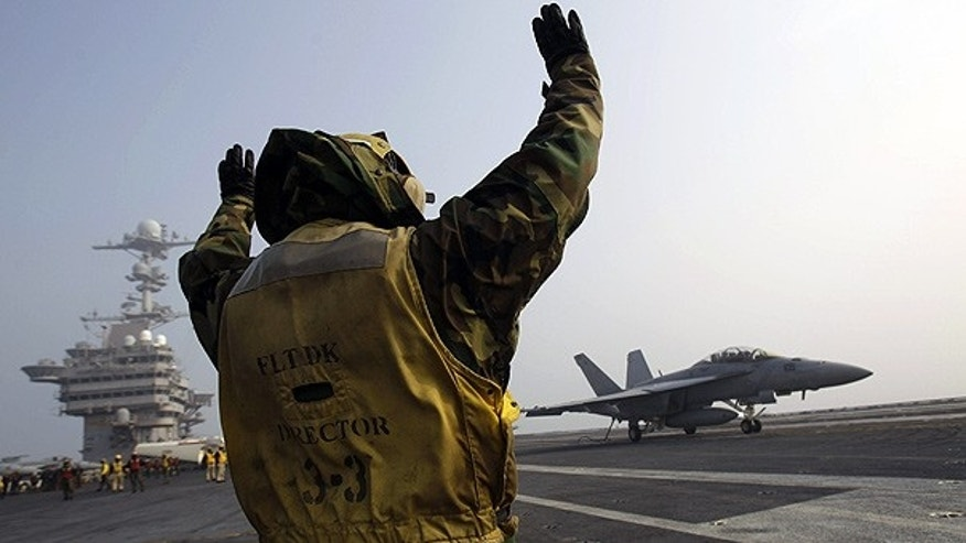 Nov. 30: Flight deck crew signals as a U.S. Navy F/A-18F Super Hornet fighter jet lands on the deck of the USS George Washington during a joint military exercise off South Korea.