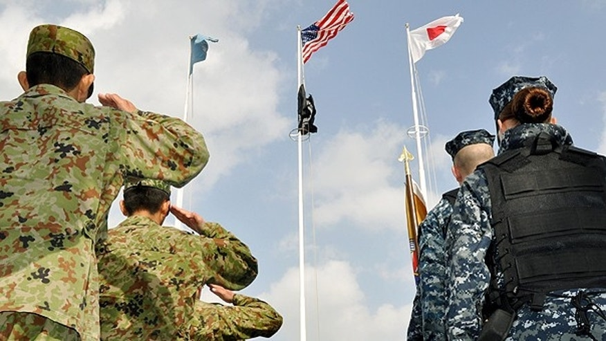 Dec. 3: Japanese Self-Defense Forces, left, and U.S. military personnel salute at the launching ceremony of a base defense exercise at the start of the annual joint military drills 'Keen Sword' in Sasebo, southern Japan.