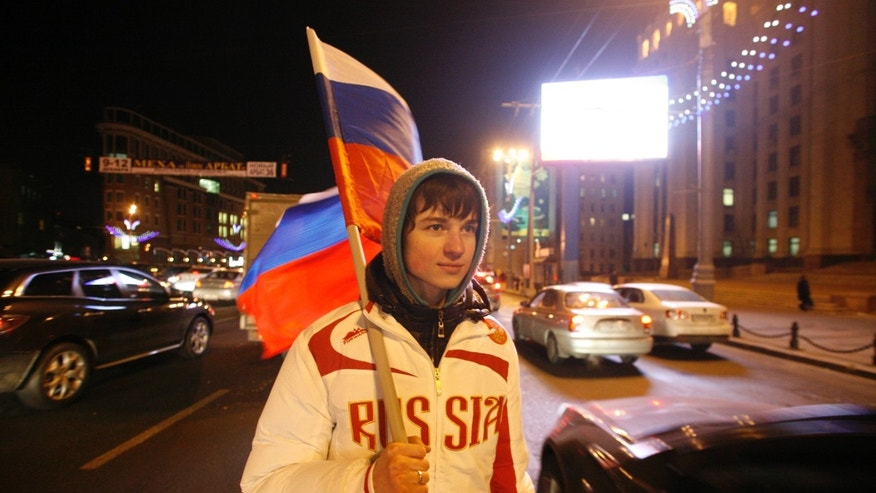 Dec. 2: A young man holding a Russian flag hands out free national flags to motorists in downtown Moscow to celebrate FIFA's selection of Russia as host to the 2018 World Cup.