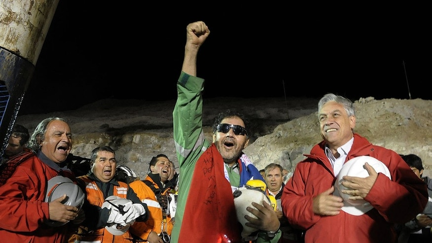 FILE - In this file photo released by the Chilean Presidential Press Office Wednesday, Oct. 13, 2010, the last miner to be rescued, Luis Urzua, center, gestures as Chile's President Sebastian Pinera, right, looks on after his rescue from the collapsed San Jose gold and copper mine where he had been trapped with 32 other miners for over two months near Copiapo, Chile. The 33 Chilean miners who captured the worlds imagination for surviving 69 days in a collapsed mine have accepted an Israeli invitation to visit the Holy Land for Christmas. Israeli foreign ministry spokesman Yigal Palmor said Tuesday, Nov. 9, 2010 that the miners had accepted the invitation. (AP Photo/Alex Ibanez, Chilean Presidential Press Office, File)