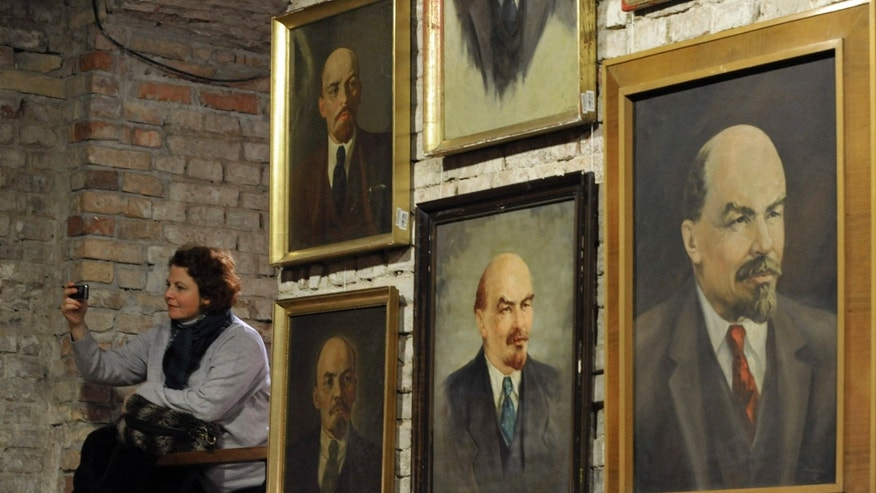 Dec. 6:  A woman takes a picture beside a wall displaying portraits of Soviet revolutionary Vladimir Lenin during their auction in the Pinter Gallery in Budapest, Hungary. More than 200 pieces of communist era relics, are being sold in an auction in benefit the victims of last month's red sludge disaster.