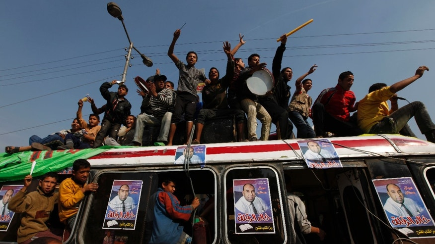 Dec. 5: Egyptian supporters of independent electoral candidate Khaled el-Zakleh tour the streets on top of a crowded bus during the runoff of the parliamentary elections in Cairo. A coalition of Egyptian rights groups on Dec. 6 urged president Hosni Mubarak to nullify the election results because of widespread vote rigging.