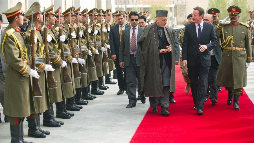Dec. 7: British Prime Minister David Cameron, center right, is greeted by Afghan President Hamid Karzai, center left, on arrival in Kabul. During Cameron's surprise trip to the country, he announced that British troops may start withdrawing from Afghanistan in 2011.