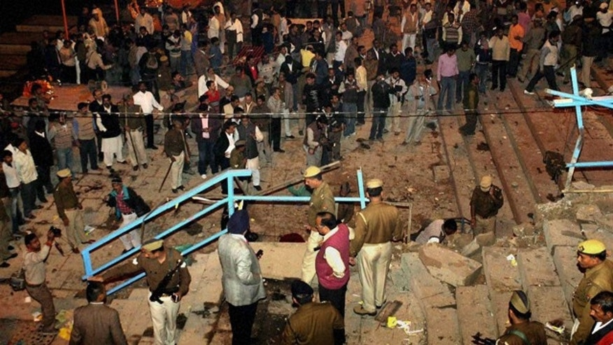 Dec. 7: People watch as policemen and officials inspect the site of an explosion in Varanasi, India.