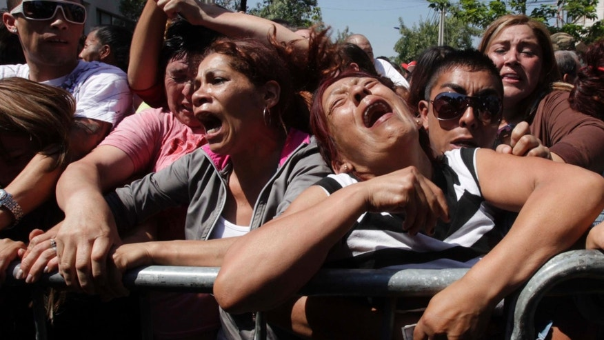 Relatives of inmates at the San Miguel prison react as they listen to the list of names of inmates who died in a fire in Santiago, Chile, Wednesday Dec. 8, 2010.  A prison fire set off during a riot killed at least 83 inmates at the Chilean prison on Wednesday and seriously injured at least 14 others, firefighters said. (AP Photo/Aliosha Marquez)