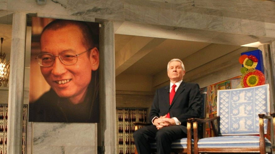 The chairman of the Norwegian Nobel Committee, Thorbjoern Jagland, sits next to an empty chair during the ceremony in Oslo City Hall to honour this years Nobel Peace Prize winner, jailed Chinese dissident Liu Xiaobo whose picture hangs at left and is represented by the empty chair.