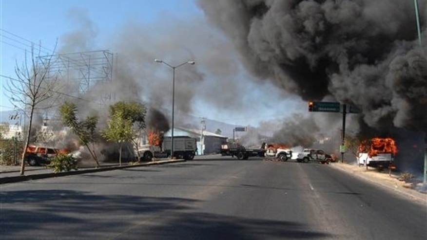 Dec. 9, 2010: Vehicles burn on a road leading to the city of Morelia, Mexico, after gunmen arrived at all five roads leading into the city, fired into the air and forced people from their vehicles.