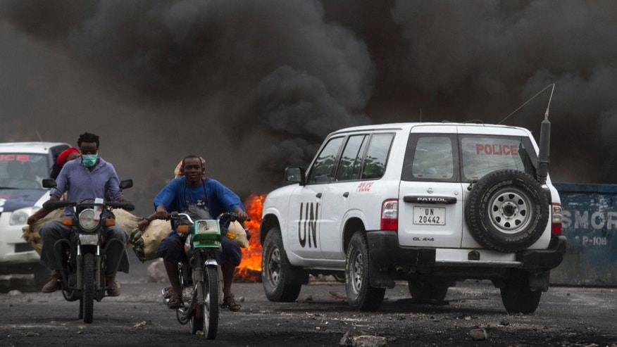 Dec. 10: Motorcycles ride next to a U.N. vehicle near a barricade set by protesters in Port-au-Prince, Haiti.