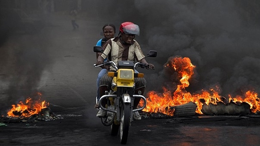 Dec. 9: A man drives a motorcycle past a barricade of burning tires in Port-au-Prince, Haiti.