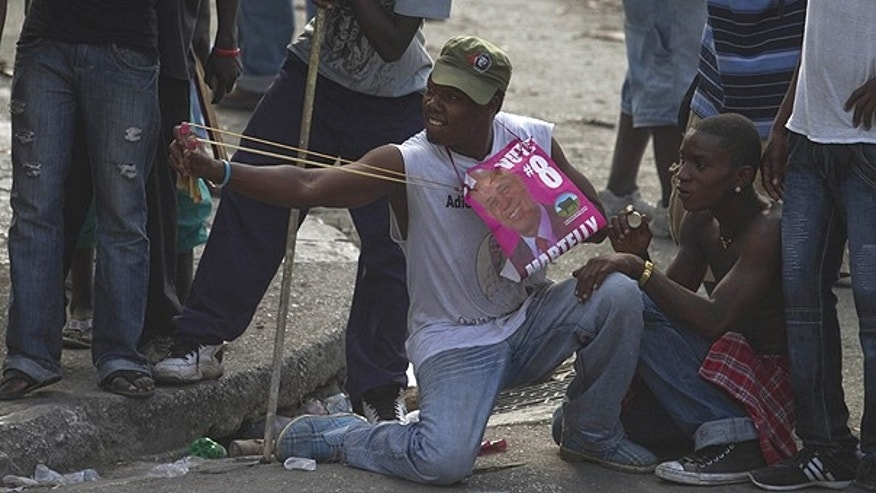 Dec. 8: Supporters of presidential candidate Michel Martelly throw stones with a slingshot at UN peacekeepers during a protest in Port-au-Prince, Haiti.