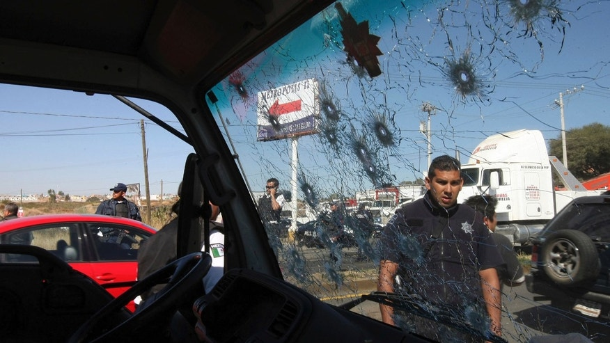 A police officer is seen through a bullet riddled truck window on a road leading to the city of Morelia, Mexico, Thursday Dec. 9, 2010. Gunmen arrived at all five roads leading into Morelia, fired into the air and forced people from their vehicles, according to Michoacan state attorney general office spokesman Jonathan Arrendondo. (AP Photo)