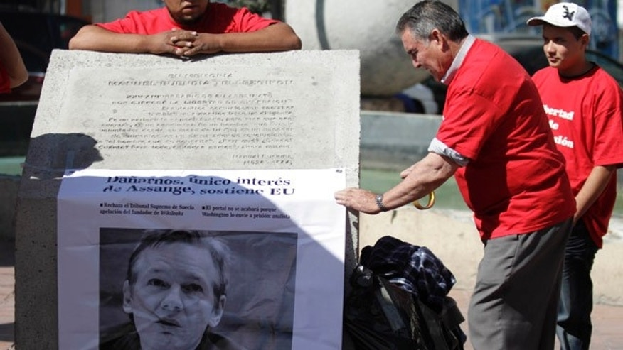 "Dec. 10: A Mexican journalist arranges a banner with an image of Wikileaks founder Julian Assange that reads in Spanish ""We are all Julian Assange,"" in Mexico City."