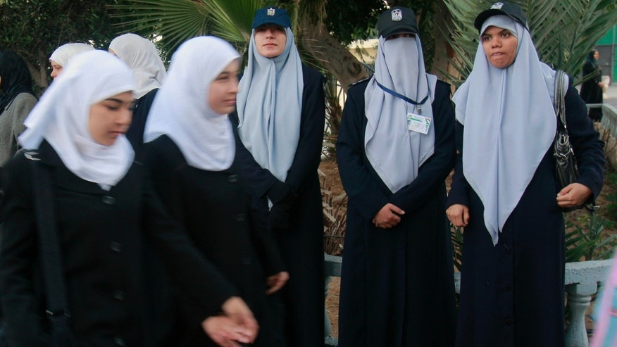 In this Dec. 9 photo, Palestinian school girls walk in front of Hamas female police officers in Gaza City. Gaza's ruling Hamas movement has embarked on a charm offensive in recent weeks.
