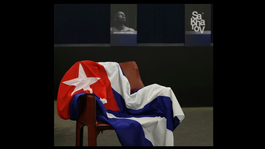 An empty chair bearing the Cuban flag and representing Cuban dissident Guillermo Farinas, is seen before European Parliament president Jerzy Buzek, back right, awarded The Sakharov Prize for Freedom of Thought to Farinas in his absence, at the European Parliament in Strasbourg, eastern France, Wednesday, Dec. 15, 2010. The European Union parliament has criticized Cuba for not allowing a dissident protester to travel to collect its biggest human rights award. (AP Photo/Christian Lutz)