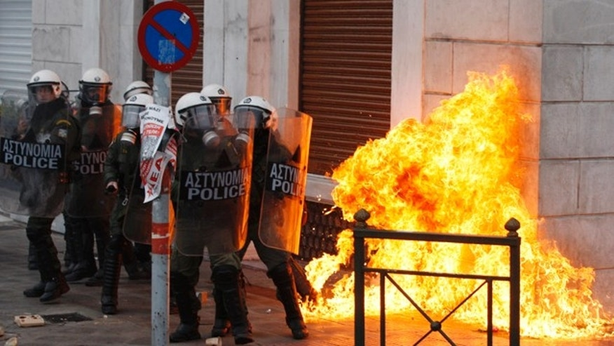 Dec. 15: Riot police try to avoid a petrol bomb outside a luxury hotel during clashes in Athens.