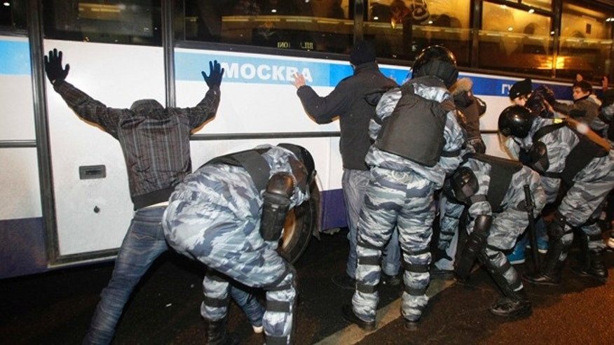 Dec. 15: Riot police officers detain protesters outside the Kievsky train station in Moscow.