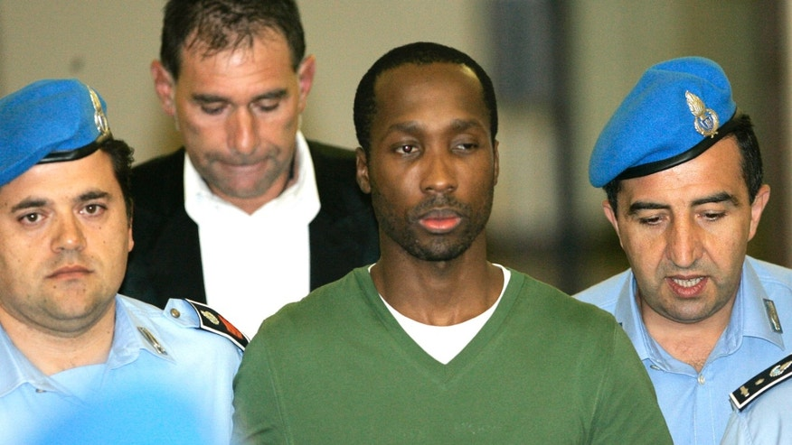 In this Sept. 16, 2008 file photo, Rudy Hermann Guede, center, is escorted by Italian penitentiary police officers after a hearing at Perugia's court, central Italy. Italy's highest criminal court on Dec. 16, 2010, upheld the conviction and 16-year prison sentence of a young man from the Ivory Coast for the 2007 murder of a British student in Perugia