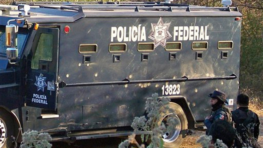 Dec. 10: Federal police agents stand next to a truck riddled with bullets in Apatzingan, Mexico.