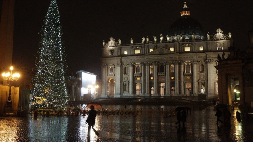 Dec. 17: People walk past the Christmas tree in St. Peter's square, at the Vatican, that was lit for the first time Dec. 17.