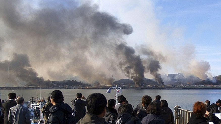 Nov. 23: South Korean villagers watch smoke rising from Yeonpyeong island after a deadly North Korea shelling.