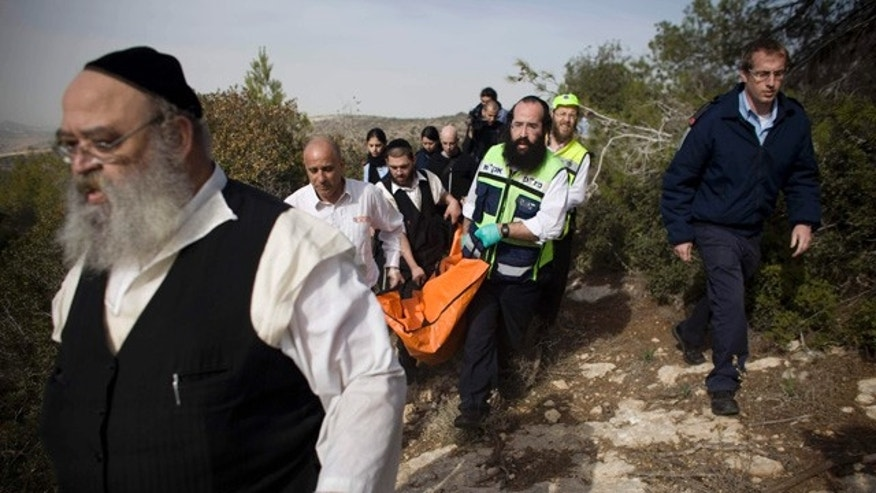 Dec. 19: Israeli rescue workers carry the body of U.S. tourist Kristine Luken after she was found in a wooded area near the village of Mata, outside Jerusalem. The body, bound and with multiple stab wounds, was found Sunday near a road outside Jerusalem, police said. Her friend, an immigrant from the U.K., had reported her missing a day earlier after she too was found nearby, also with knife wounds and her hands tied, police said. (AP)