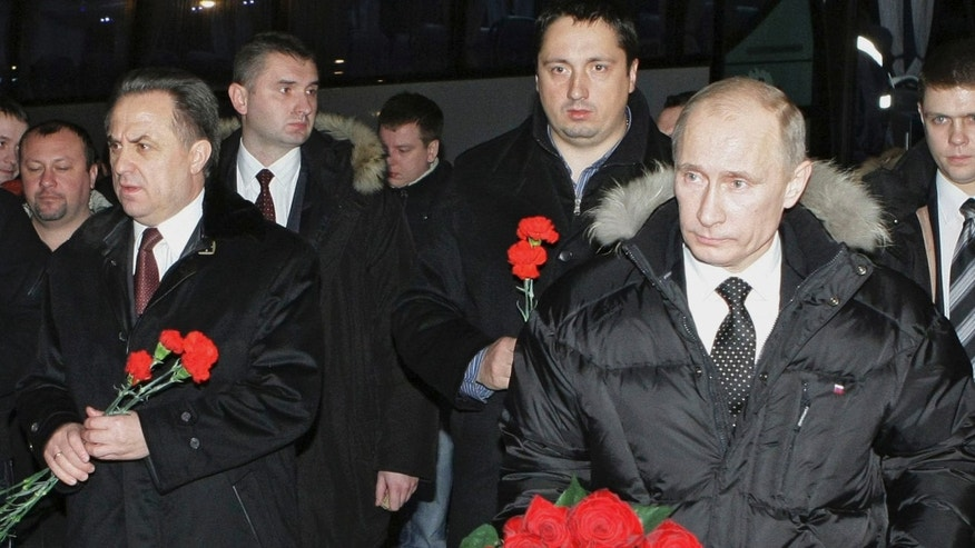 Dec. 21: Russian Prime Minister Vladimir Putin, Sports Minister Vitaly Mutko and the head of the soccer fans association Alexander Shprygin walk to lay flowers at the grave of a soccer fan Yegor Sviridov, 28, who was killed on Dec. 6 in an attack on soccer supporters, Moscow, Russia.