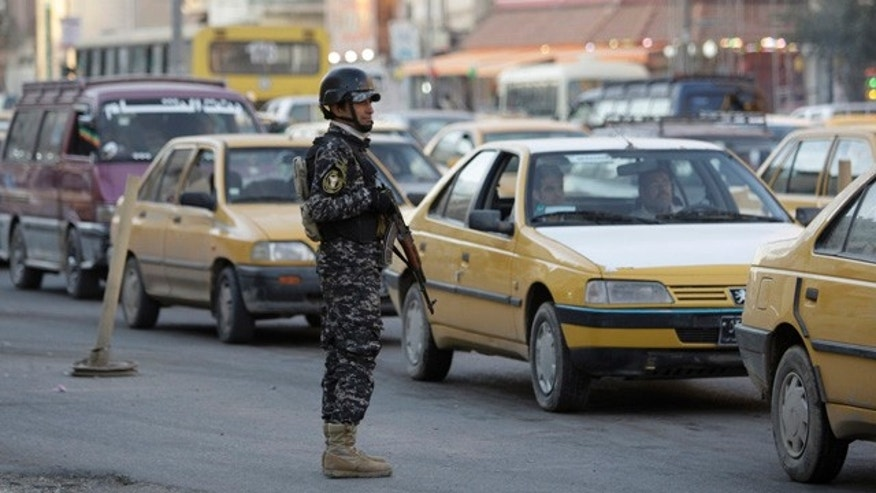 Dec. 28: An Iraqi policeman stands guard while hundreds of vehicles are in queue, waiting to be searched, at a checkpoint in Baghdad, Iraq, on Tuesday. Security officials are investigating the possibility of removing some of the hundreds of checkpoints across the city, in a sign of the improving security situation. The checkpoints are designed to catch insurgents, but they also slow down traffic in the already congested city. (AP)