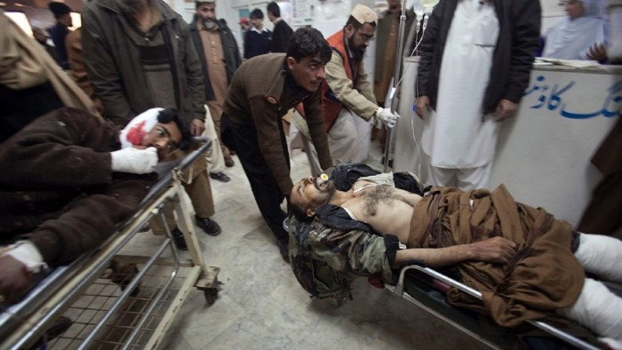 Dec. 25, 2010: Men injured in a suicide bomb attack in Pakistan's northwest Bajaur region are brought to Lady Reading Hospital in Peshawar for treatment. A burqa-clad bomber attacked a crowd of people waiting for aid in Pakistan on Saturday, killing at least 40 of them, officials said, showing militants' ability to strike despite army offensives.