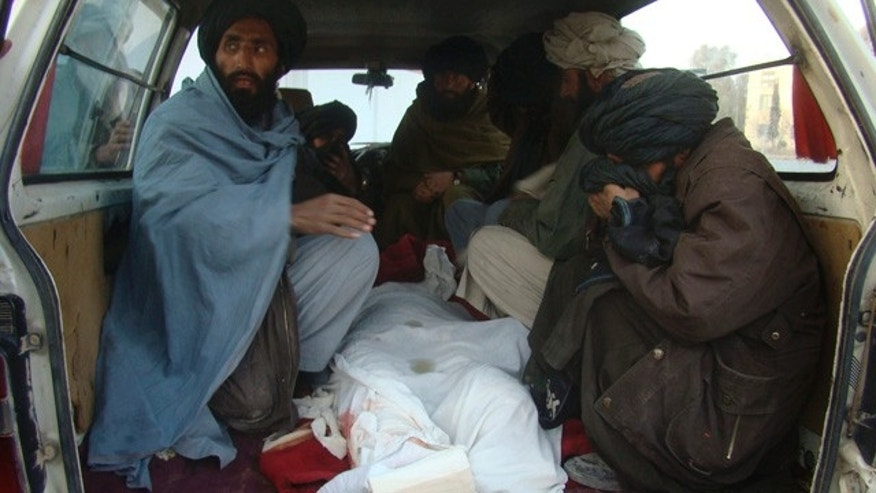 Dec. 30: The body of a roadside bomb blast victim lies in a vehicle as Afghan men mourn next to it at a hospital in Lashkar Gah, Helmand province southern Afghanistan. A roadside bomb blew up next to a minibus at a crowded intersection on a major highway in southern Afghanistan on Thursday, killing civilians, officials said. (AP)