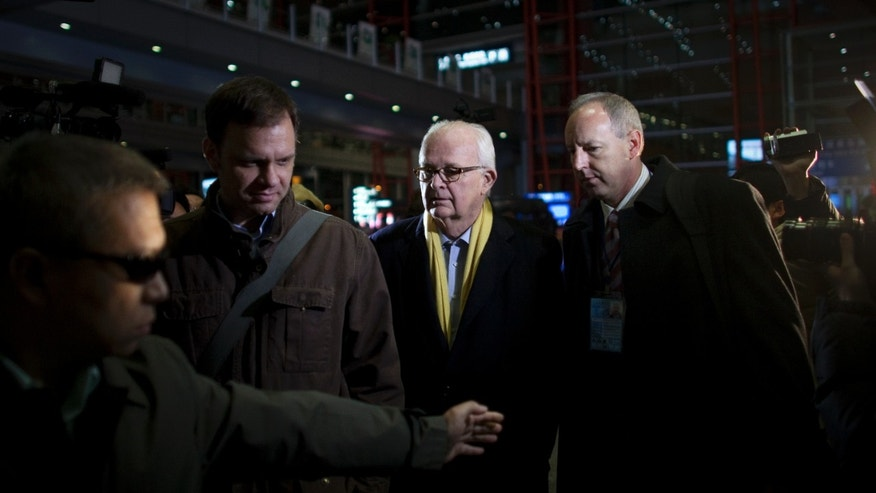 Jan. 5: A body guard, left, tries to shield off journalists while U.S. special envoy for North Korea Stephen Bosworth, second right, walks out of an exit upon arrival at the Capital Airport in Beijing, China. Bosworth, Obama's envoy for North Korea sought to calm fears of war on the Korean peninsula.