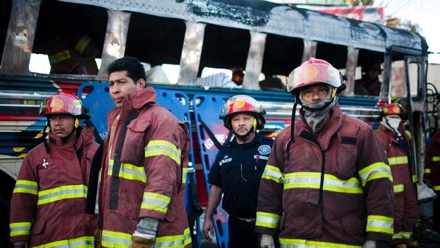 Firefighters rest after extinguishing a fire inside a bus caused by an explosion where five people died and 16 were injured in Guatemala City, Monday Jan. 3,  2011. The cause of the explosion is unknown. (AP Photo/Rodrigo Abd)