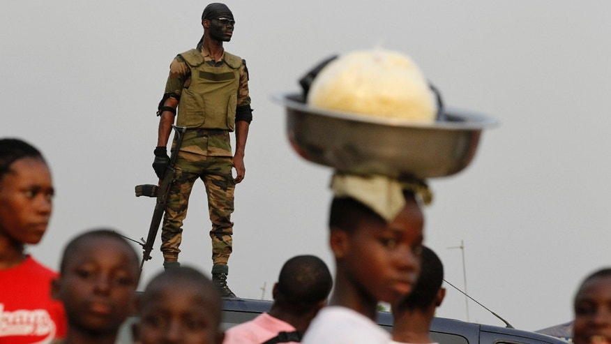 Jan. 5, 2011: A member of the security forces stands guard as people gather for a rally by youth leader Charles Ble Goude in support of Laurent Gbagbo, who recently named Goude to his cabinet, in the Koumassi neighborhood of Abidjan, Ivory Coast. While the United Nations and other world powers recognize rival Alassane Ouattara as the winner of November presidential elections, Gbagbo has refused to step down for more than a month after the presidential runoff vote. The 15-nation regional bloc ECOWAS (The Economic Community Of West African States) has threatened to remove the incumbent leader if ongoing negotiations fail.